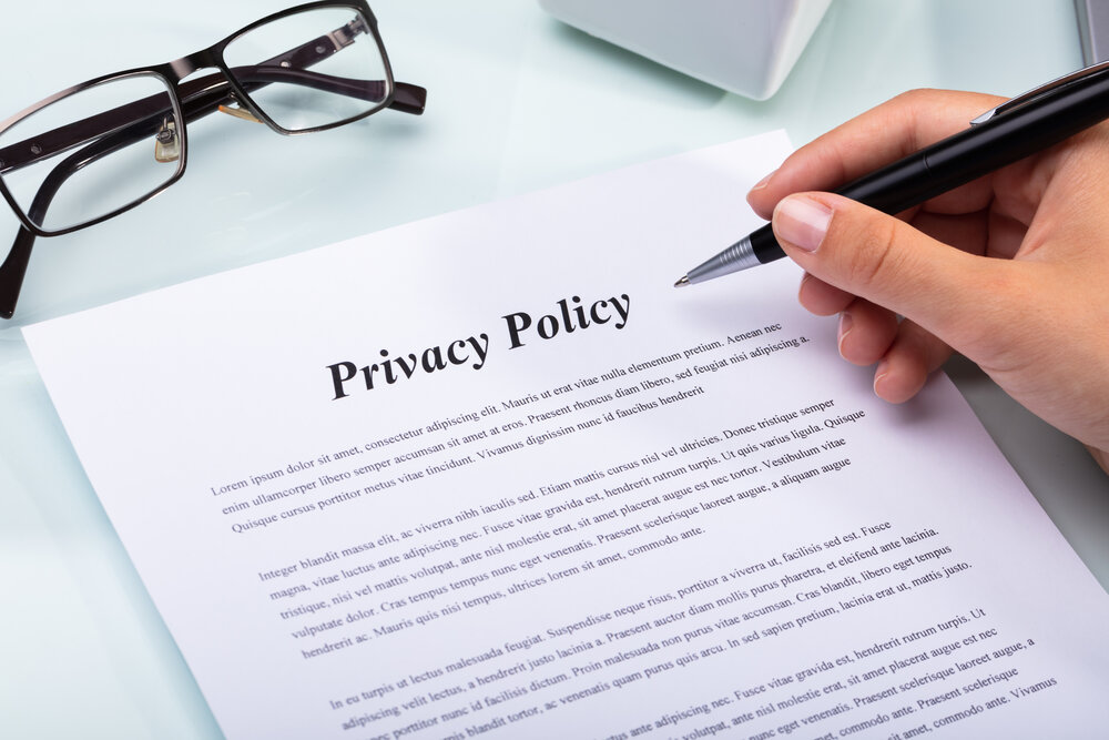 External Privacy Policy with hand hovering above it and reading glasses sitting on it