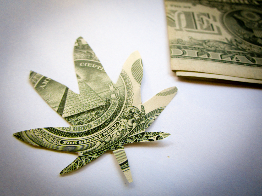 Cannabis leaf shape cut out of a US dollar bill to demonstrate growth of cannabis business