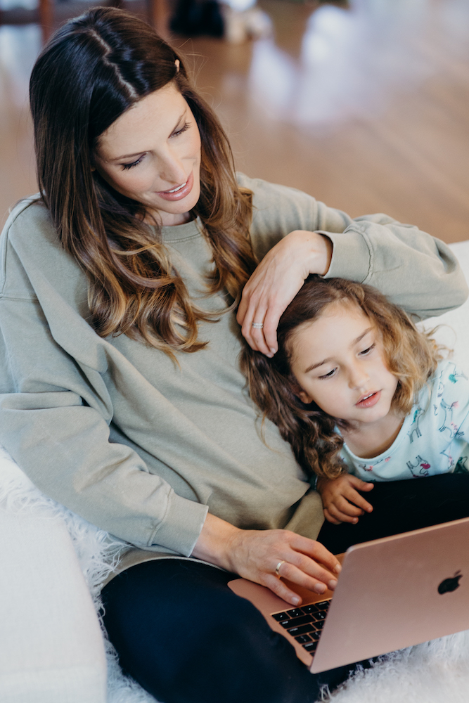 Noam with her child working from home on her Macbook