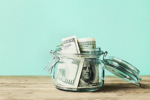 Dollar bills in a mason jar on a wooden table signifying saving money due to small business relief grant in California