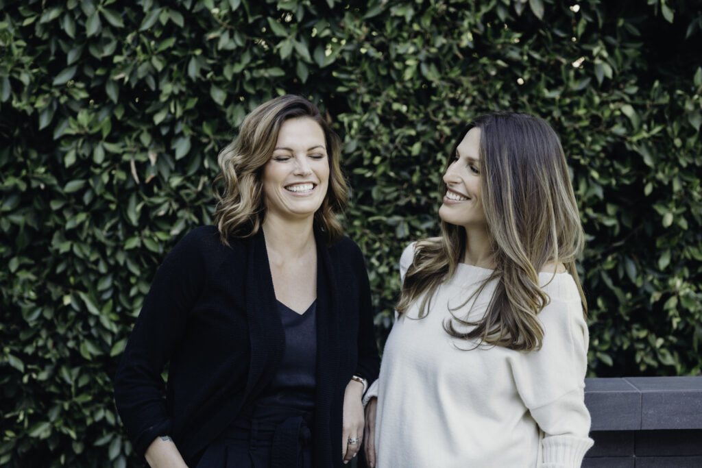 CGL's female founders, Hannah Genton and Noam Cohen, smiling in a garden landscape.