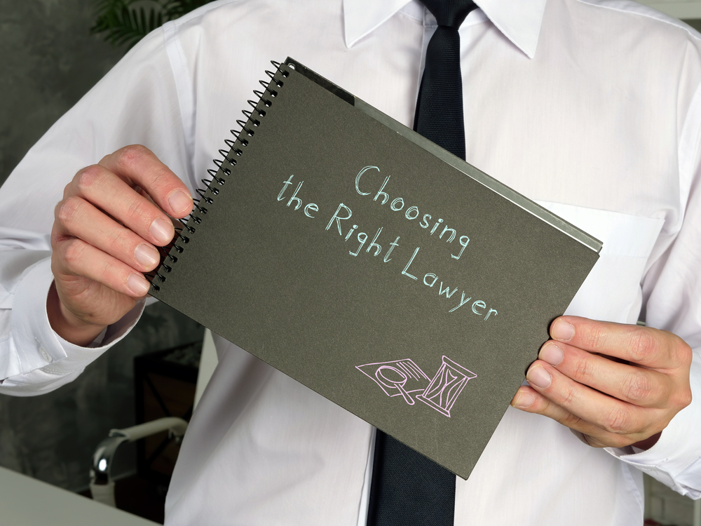 """Businessperson holding a notebook inscribed with """"Choose the Right Lawyer'"""
